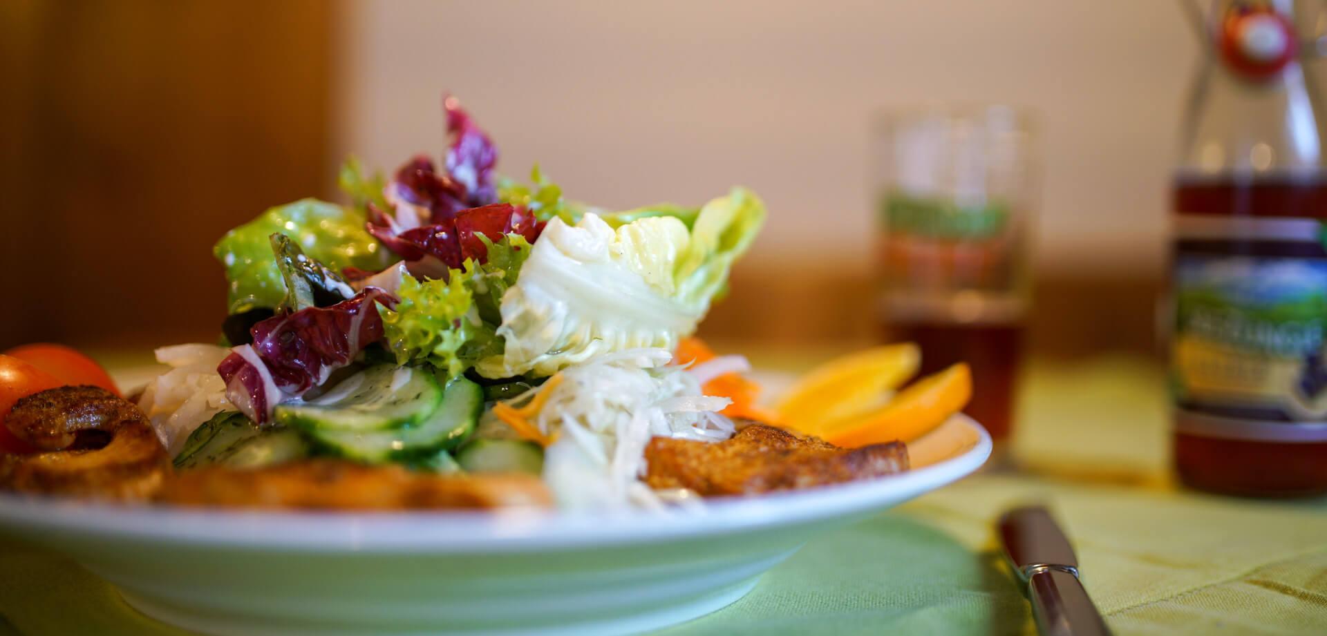 Salatteller mit Putenbruststreifen auf Tisch in Wirtchaft
