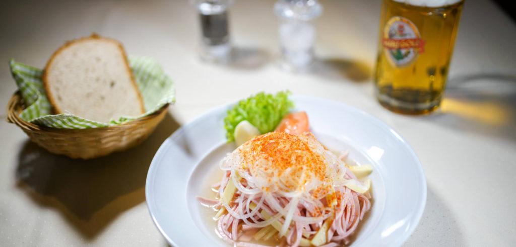 Wurstsalat mit Brot auf Tisch